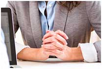 Woman sitting at a desk with hands crossed